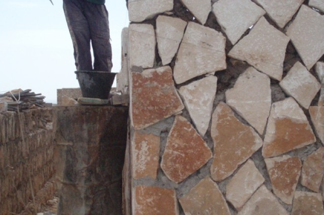 A Socotran contractor adds cement and positions stones for the walls of one of the two schools being built in the towns of Usama Bin Zaid and Omar Al Kittab.
