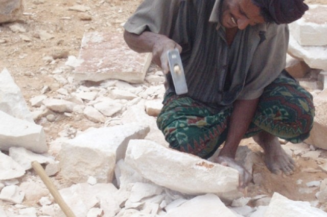 A Socotran contractor shapes stones from the local area for the walls of two schools being built in the towns of Usama Bin Zaid and Omar Al Kittab.