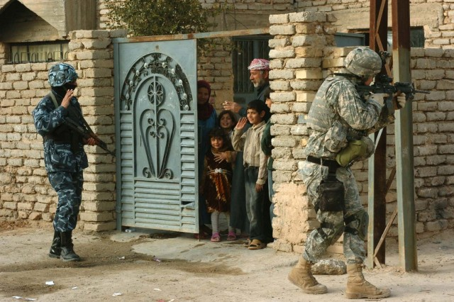 An Iraqi policeman waves to a family while conducting a joint patrol in Samarra, with Soldiers from Company C, 2nd Battalion, 505th Parachute Infantry Regiment on Jan. 30.