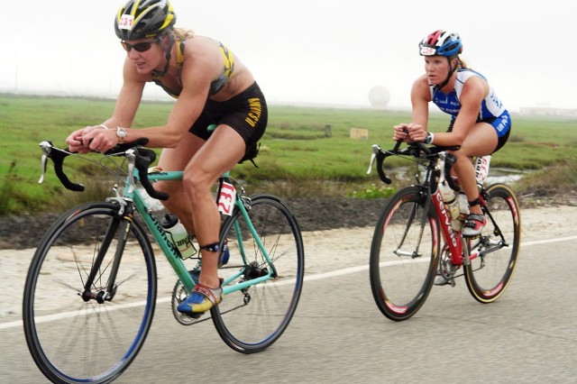 "Lt. Col. Heidi Grimm of the U.S. Army World Class Athlete Program who is stationed in Fort Carson, Colo., leads Air Force Capt. Lara Brown of Los Angeles Air Force Base during the bike portion of the 2006 Armed Forces Triathlon Championships at Naval Base Ventura County in Point Mugu, Calif. Grimm and Brown finished first and second respectively in the women's division of the 1,500-meter swim, 24.8-mile bike and 6.2-mile run. Grimm later was named 2006 Amateur Female Triathlete of the Year by ""Triathlete"" magazine."