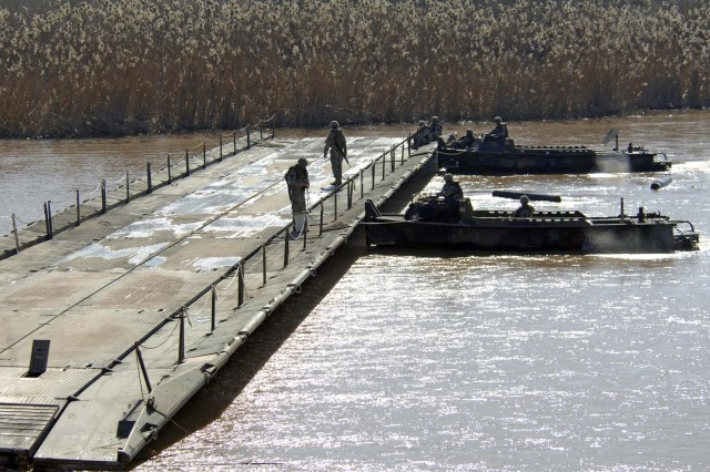 Soldiers guide the newly assembled assault float bridge section upstream.