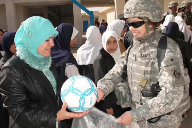 Col. Debra M. Lewis, commander of Gulf Region Division's Central District, Army Corps of Engineers, presents soccer balls to the headmistress of a new girls high school in north Baghdad Feb. 5.