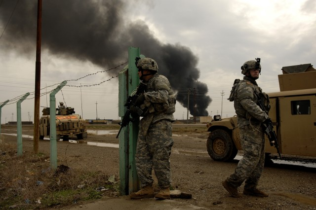 Soldiers stand guard while waiting for Iraqi police to lead a patrol in Riyahd, Iraq. The Soldiers are from Company D, 2nd Battalion, 27th Infantry Regiment, 3rd Brigade Combat Team, 25th Infantry Division.
