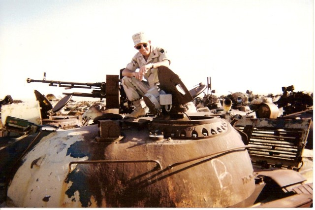 Chief Warrant Officer Robert Rangel on top of a tank at the tank graveyard in Camp Doha Kuwait during one of his 11 deployments.