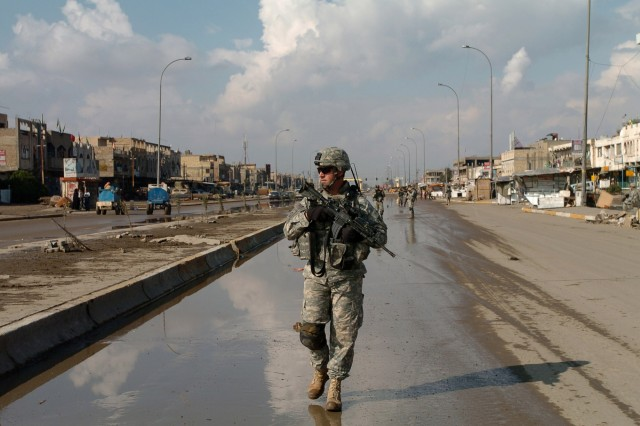 Staff Sgt. Steven Michaelis, a squad leader from Battery B, 2nd Battalion, 319th Airborne Field Artillery Regiment, 2nd Brigade Combat Team, 82nd Airborne Division, takes the point as his platoon moves down a street in Adhamiyah.