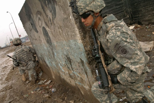 """Spc. Martin Garza, an artilleryman with Battery B, 2nd Battalion, 319th Airborne Field Artillery Regiment, 2nd Brigade Combat Team, 82nd Airborne Division, and a fellow Soldier patrol Adhamiyah, known as an IED """"hot spot"""" Feb. 16."""