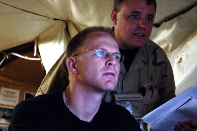 Maj. Dan Church (left) and Lt. Col. David Condie review CT scans and X-rays on current patients at the Air Force Theater Hospital Feb. 19 at Balad Air Base, Iraq. The radiology staff has two new 16 slice CT scanners that expedite the process from 90 minutes to about 10 minutes. Major Church and Colonel Condie are assigned to the 332nd Expeditionary Medical Group.
