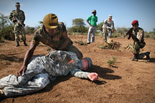 2nd Cpl. Teklay Atsbaha learns to search a simulated suspect while other students provide backup security. The second corporal rank is used in Ethiopia.