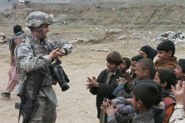 Staff Sgt. Justin Holley shows the local children how to do a hand-twist puzzle.