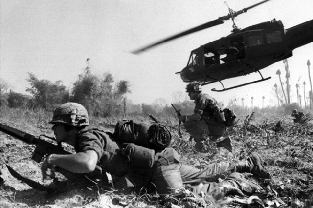 Major Bruce Crandall's UH-1D helicopter climbs skyward after discharging a load of infantrymen on a search and destroy mission.