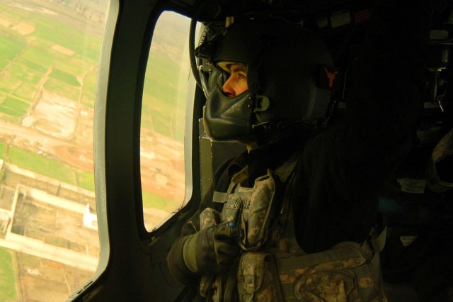 Sgt. Travis Danley, a Black Hawk helicopter crew chief with the 82nd  Airborne Division, scans the horizon while on the way to pick up a casualty near Forward Operating Base Salerno, Afghanistan, Feb. 5. Paratroopers from the division who are involved in tragic incidents are given critical-event debriefings so they can successfully cope with battlefield conditions.