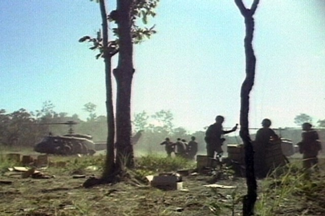 During the fight for LZ X-Ray in the Ia Drang Valley of Vietnam, the wounded are rushed to the waiting UH-1 of the 229th Assault Helicopter Battalion.  Photo extracted from US Army motion picture footage. (Nov 1965) ""