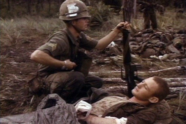 A wounded Soldier of the 1st Battalion, 7th Cavalry, is watched over by a fellow comrade during the fight for LZ X-Ray in the Ia Drang Valley of Vietnam.  Photo extracted from US Army motion picture footage. (Nov 1965)""