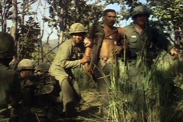 A wounded Soldier of the 1st Battalion, 7th Cavalry, is assisted by two fellow comrades during the fight for LZ X-Ray in the Ia Drang Valley of Vietnam.  Photo extracted from US Army motion picture footage. (Nov 1965)""