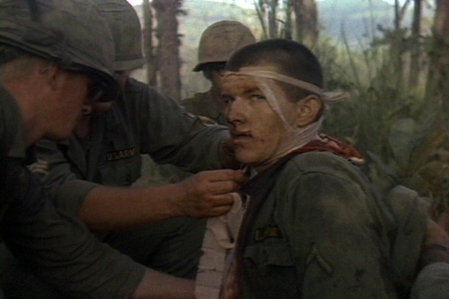 A wounded Soldier of the 1st Battalion, 7th Cavalry, is attended to by fellow comrades during the fight for LZ X-Ray in the Ia Drang Valley of Vietnam.  Photo extracted from US Army motion picture footage. (Nov 1965)""