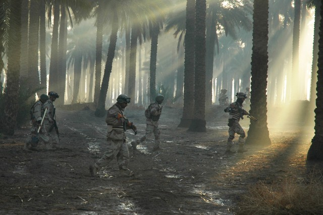 "Soldiers from 3rd Battalion, 4th Brigade, 6th Iraqi Army Division (the ""Baghdad Eagles"") move stealthily through a palm grove on a late February patrol in the area of Mahmudiayh, 17 miles south of Baghdad. Soldiers from the 10th Mountain Division are nearby, in support of the operation, aimed at finding anti-Iraqi forces and their weapons."