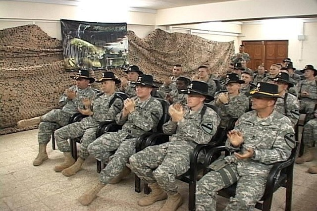 Soldiers from the 1st Air Cavalry Brigade, 1st Cavalry Division, at Camp Taji, Iraq, pay tribute to Medal of Honor recipient retired Lt. Col. Bruce Crandall during a live broadcast of the ceremony Feb. 26. Crandall helped begin the implementation of air assaults in combat, which are still carried out today by 1st ACB in Iraq.