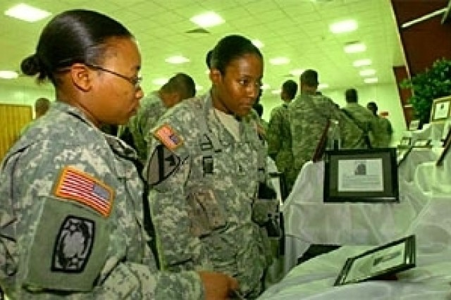 Capt. Latonya Jones and Chief Warrant Officer 2 Betty Fisher look through a display of famous African-American icons at Forward Operating Base Prosperity in Baghdad Feb. 16.