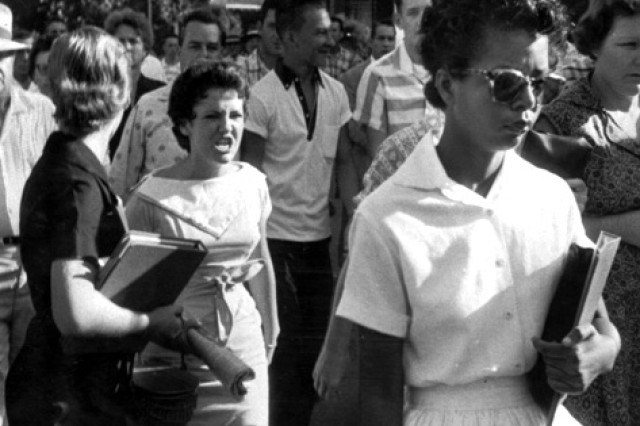 Sept. 4, 1957 - Students of Central High School in Little Rock, Ark., including Hazel Bryan, second left, shouts insults at Elizabeth Eckford, second right, walking past a line of National Guardsman, not shown, who blocked the main entrance of the school. One of nine black children who endured angry white mobs to integrate a Little Rock, Arkansas high school in 1957.