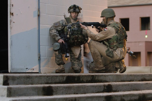 A Fort Polk Soldier, role playing as a member of the Iraqi Army, pulls security on a doorway during a raid on Leschi Town with the 4th Brigade, 2nd Infantry Division, at Fort Lewis, Wash.