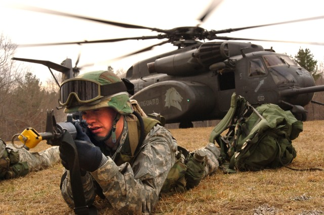 A Soldier pulls security after dismounting an HM-53E Sea Dragon helicopter during military operations in urban terrain training.