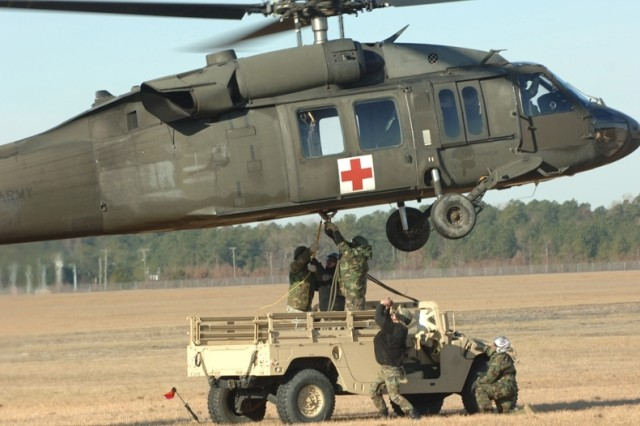 Soldiers hook up a Humvee to a UH-60 Black Hawk helicopter for sling-load transport.