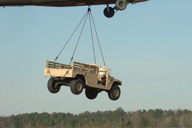 The Black Hawk helicopter lifts off with the sling load.