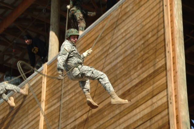 Soldiers rappel from a platform.