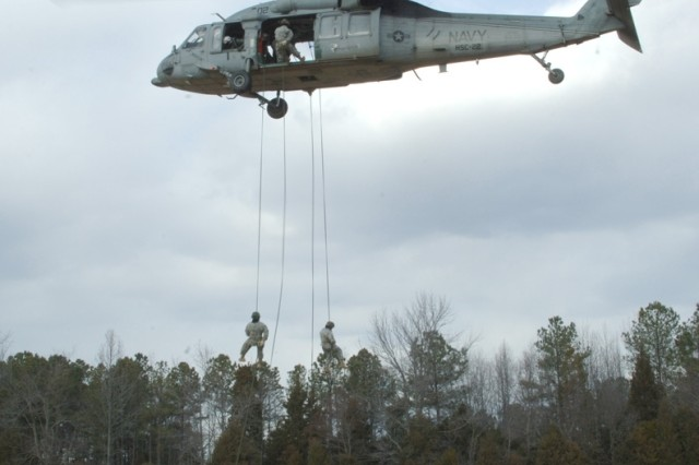 Soldiers rappel out of a Navy helicopter.