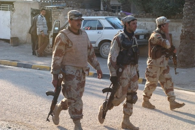 Iraqi Soldiers, backed by their U.S. counterparts, walk through the neighborhoods.