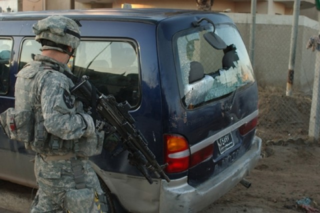 A Soldier mans a blocking position. The window of the vehicle was shot out by insurgents.