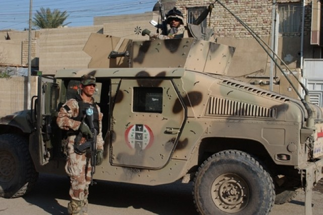 Iraqi Soldiers from 3rd Battalion, 2nd Brigade, 7th Iraqi Army Division stand guard alongside their Humvee during a security stop.