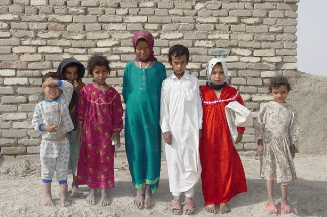 Iraqi children pose in front of a stone wall.