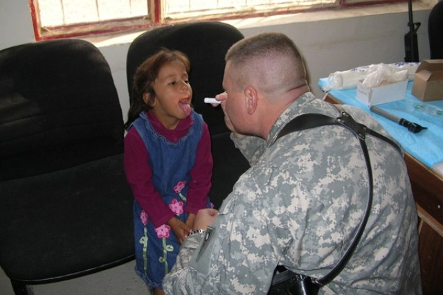 A Soldier performs a medical examination on an Iraqi girl.
