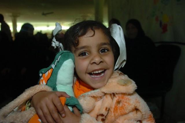 An Iraqi girl smiles as she hugs her stuffed animal.