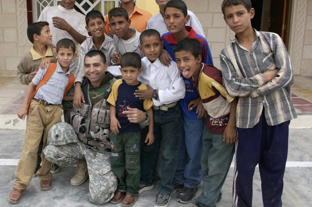 Lt. Col. Lorenzo Valenzuela, Army Corps of Engineers, Multinational Division-Central South, poses for a photo with Iraqi children prior to the ribbon cutting ceremony for the Salah Hadi Obid Elementary School in Afak. Projects like this are being completed throughout Iraq with little or no press coverage.