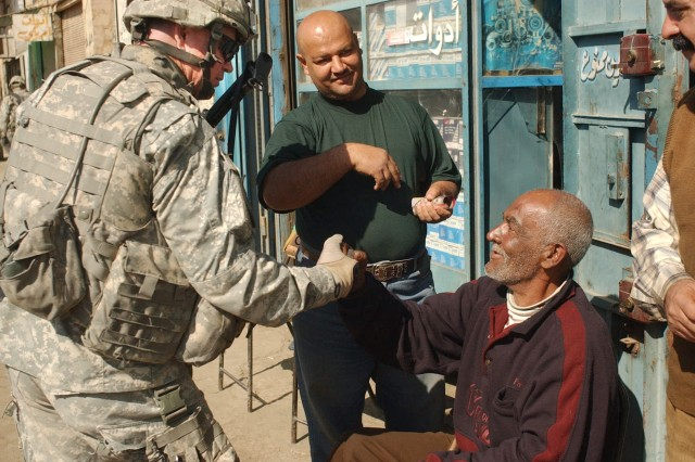 Sgt. 1st Class Marc Biletski, from Company B, 1st Battalion, 23rd Infantry Regiment, 2nd Infantry Division, greets an Iraqi civilian during a cordon and search mission with Iraqi Soldiers in Rusafah.