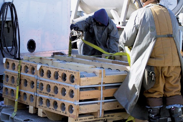 Workers prepare a pallet of M-55 VX nerve-agent filled rockets for transport from the chemical agent storage area to a nearby disposal facility for destruction.