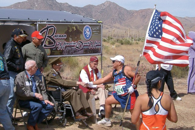 A competitor takes a moment to greet a death march suvivor, who wears his World War II uniform for the occasion.