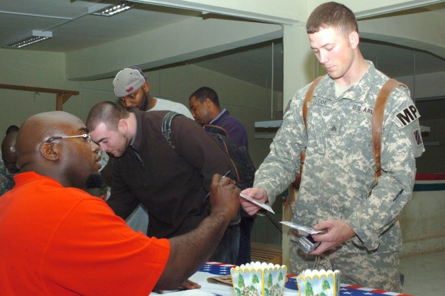 Sgt. Derek Briscoe, 727th Military Police Detachment, stops at the Area 51 MWR facility at Camp Victory to see Kansas City Chiefs' guard Will Shields. Shields joined Alge Crumpler, Shelton Quarles and Ben Watson on a 12-day trek through the Middle East, made possible by USO.