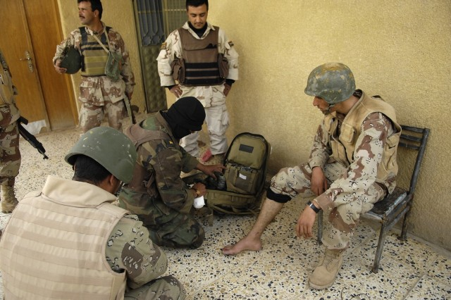 An Iraqi medic treats an Iraqi Soldier who was shot in the toe.