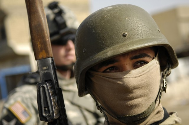 An Iraqi Soldier keeps an eye out for trouble.