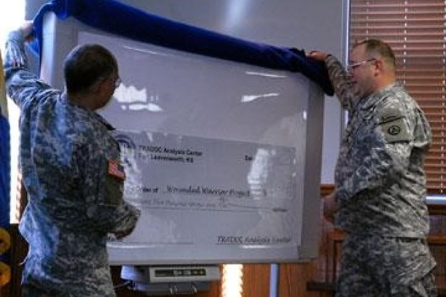 Lt. Col. Frank Villanueva, senior military analyst in the Scenarios and Wargaming Directorate of the TRADOC Analyst Center, and Lt. Col. John Hughes, TRAC operations research analyst, unveil a check to the Wounded Warrior Project for nearly $5,000 during a presentation Feb. 28 in McNair Hall.