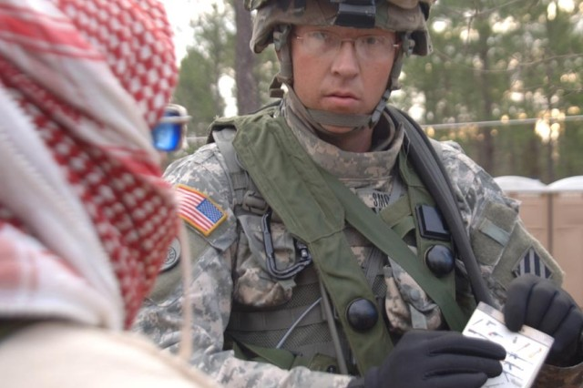 A Soldier uses picture cards to get his message across to an Arab speaking role-player.