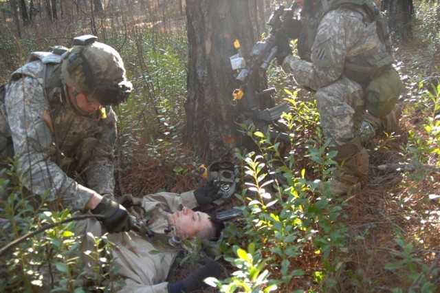 A Soldier searches the body of a role-playing dead insurgent, killed during a simulated firefight.