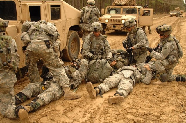 """Soldiers treat the """"wounded"""" after they were hit by a mock roadside bomb."""