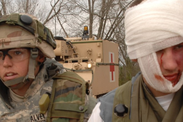 Sgt. Alvey, a medic, escorts a role-playing injured Iraqi civilian to a medical vehicle during a mission readiness exercise at Fort Stewart, Ga., March 2. The Soldiers, all from the 3rd Infantry Division, are preparing for a deployment to Iraq.
