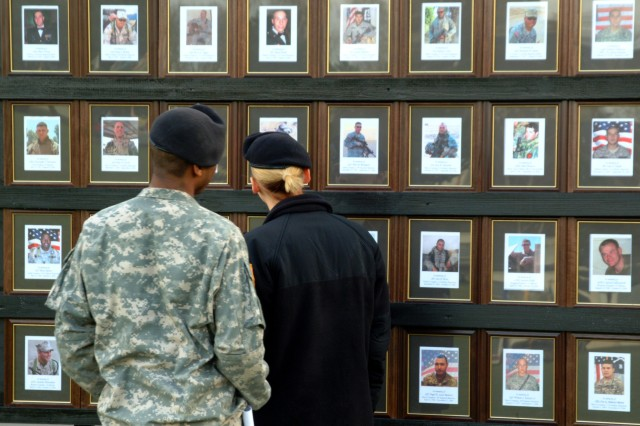 Soldiers look at a display honoring fallen comrades from the 1st Armored Division, March 6, at Ray Barracks in Friedberg, Germany. The division returned from Iraq in February after a 14-month deployment.