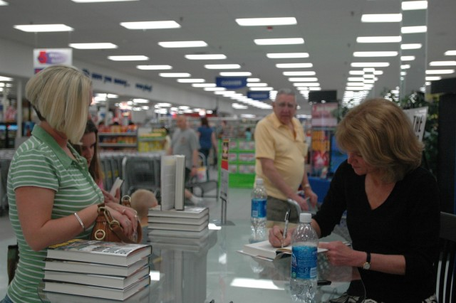 "Martha Raddatz, the senior White house correspondent for ABC News, signs her new book, ""The Long Road Home,"" March 10 at the Clear Creek Post Exchange. The book documents the First Team's April 2004 battle in Sadr City that killed eight troopers and wounded more than 60 others."