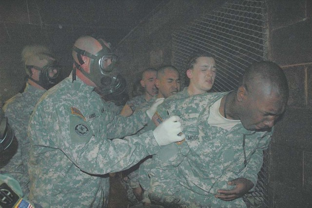 Staff Sgts. David Little, left front, and Shaun Harris, Company A, 2nd Battalion, 60th Infantry Regiment drill sergeants, encourage Pvts. Brandon McGowan, Stephanie McChristian, Ivan Vital and Richard Hernandez to say the Soldier's Creed after removing their protective masks in the NBC chamber.